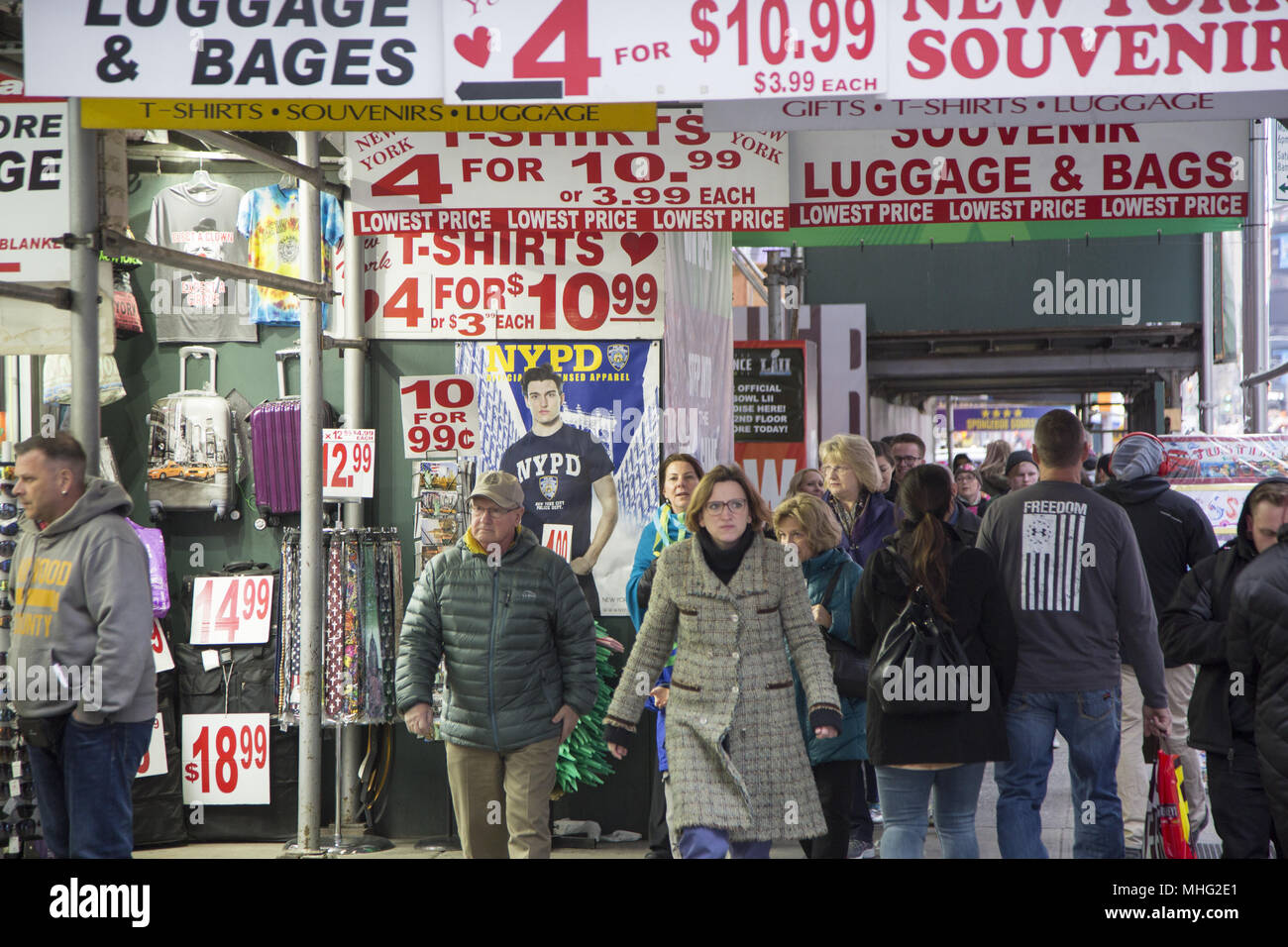 People walk past shops selling souvenirs and luggage geared for tourists in the Timnes Square neighborhood along 7th Avenue in midtown Manhattan. - Stock Image