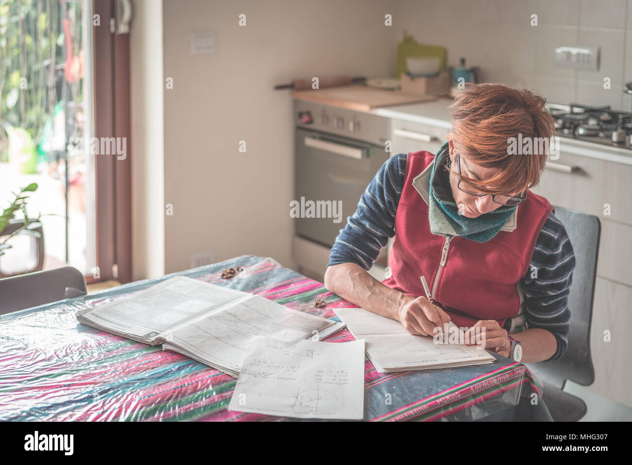 Woman with eyeglasses sitting at table, reading and handwriting paperwork and documents. Selective focus, home interiors. Concept of working at home. - Stock Image