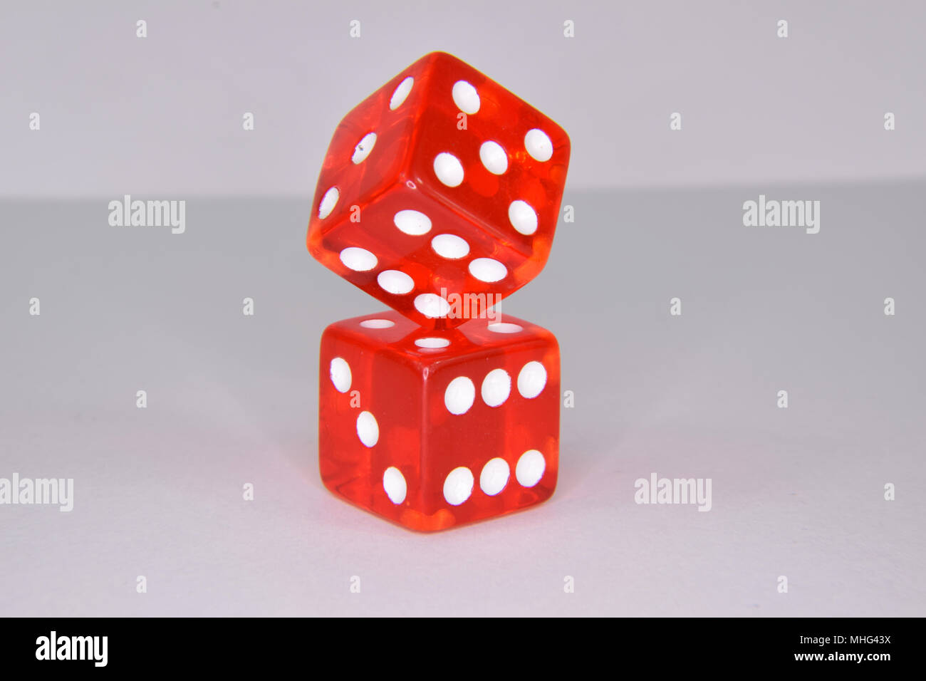 Stacked and balancing red luminescent casino gambling dice - isolated Stock Photo