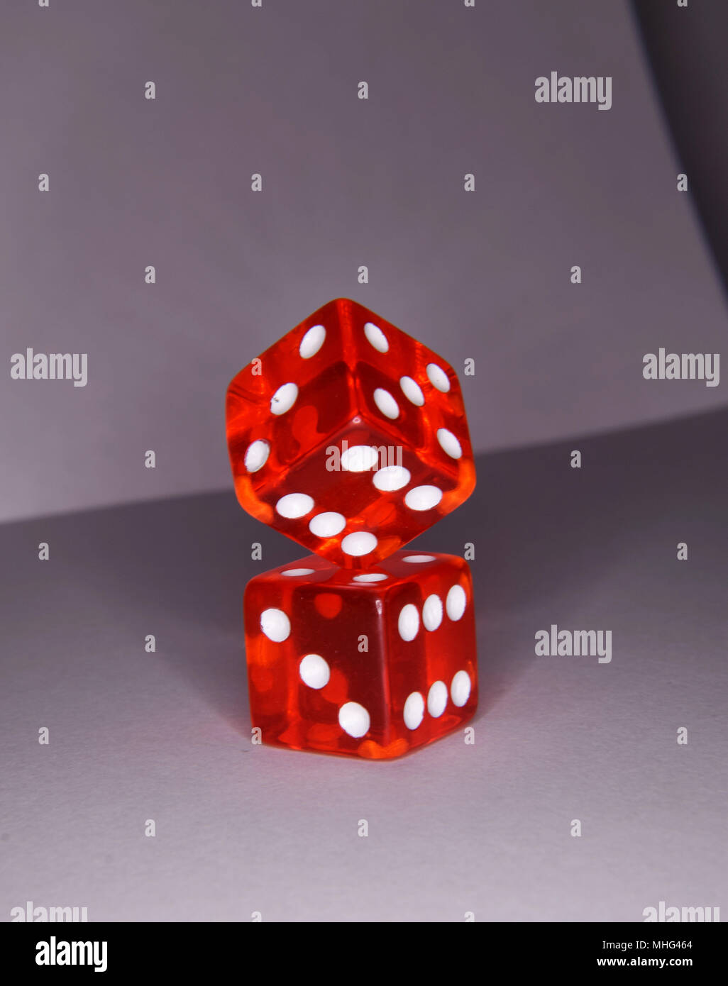 Balancing red luminescent casino gambling dice - vibrant colors and box composition Stock Photo