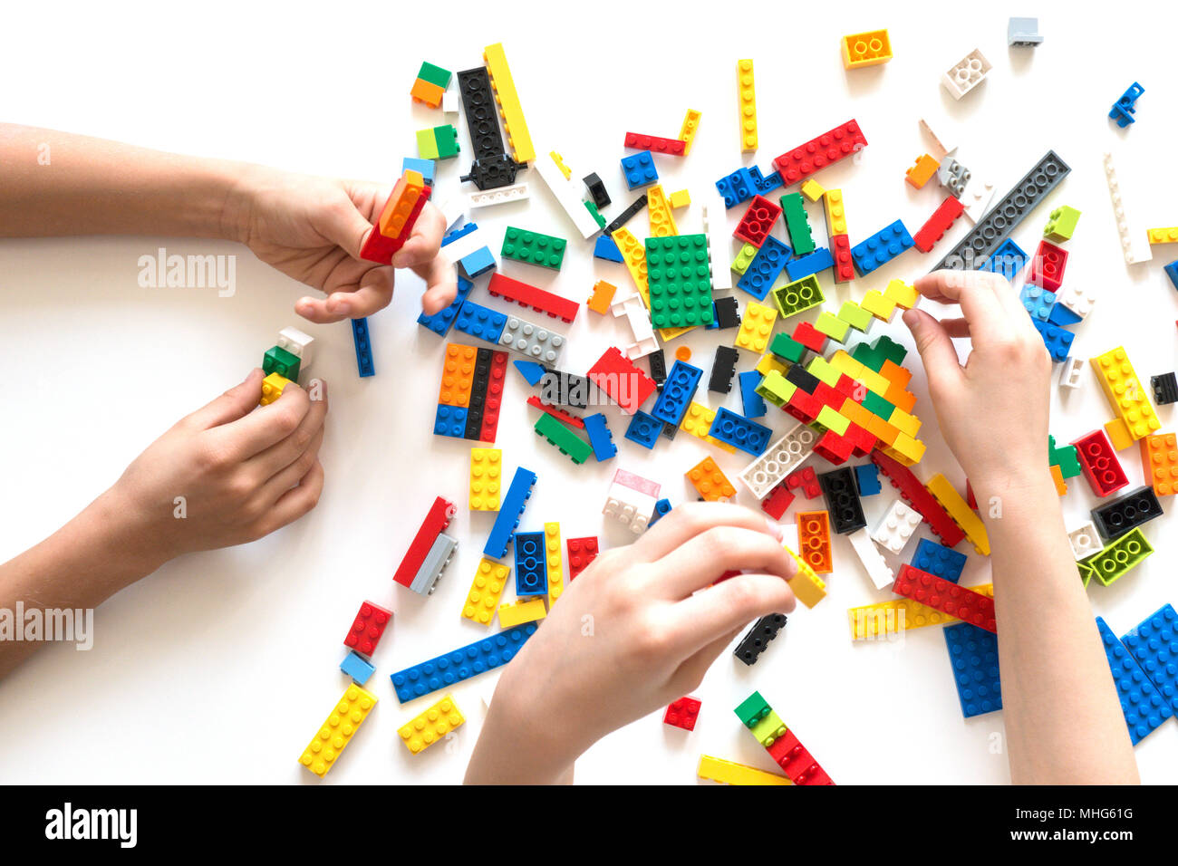 Children Hands Play With Colorful Lego Blocks On White Table