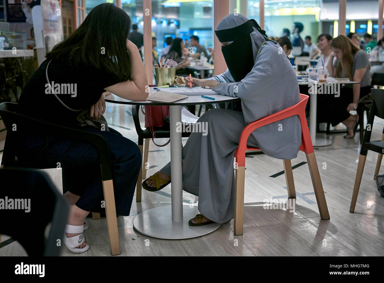 Muslim woman dressed in a traditional Burka studying in a cafe interior. Thailand Southeast Asia - Stock Image