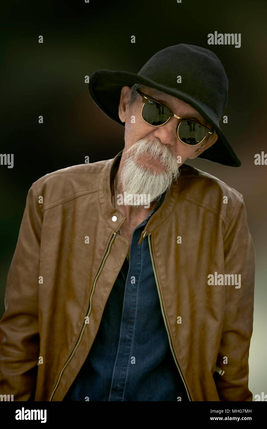 Portrait of an Asian elderly man isolated against a plain background - Stock Image