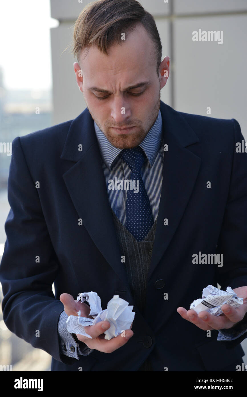 businessman emotionally  tear and eat paper documents - Stock Image