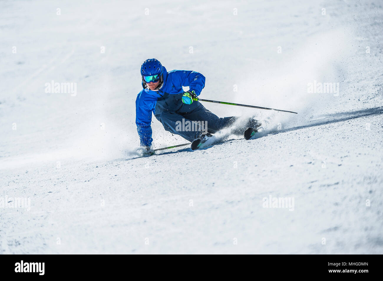 A male skier carving turns on a piste in the French alpine resort of Courchevel. Stock Photo