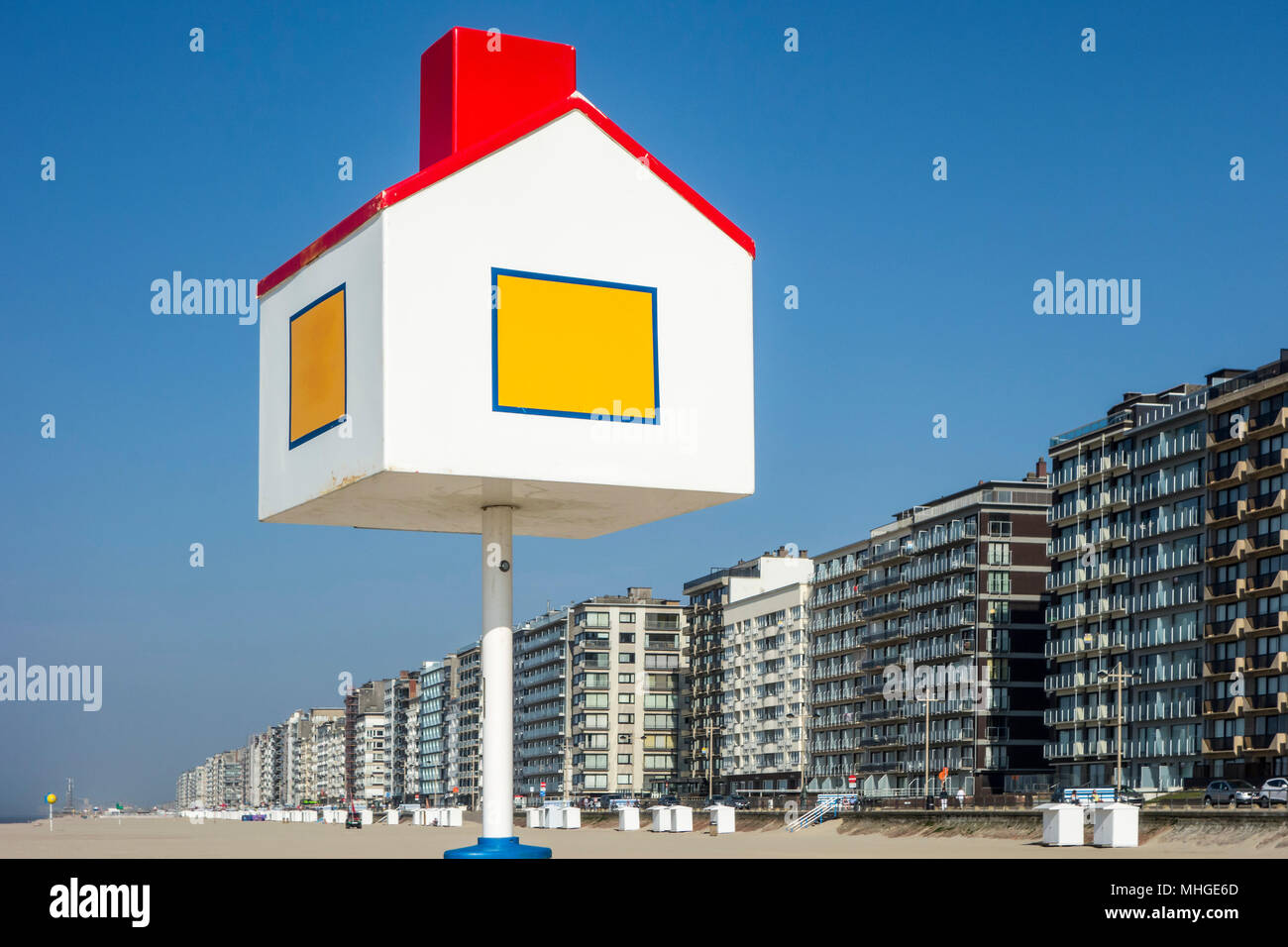 Reference point in the shape of a house for children at the beach and flats / apartment blocks at seaside resort Middelkerke, West Flanders, Belgium - Stock Image