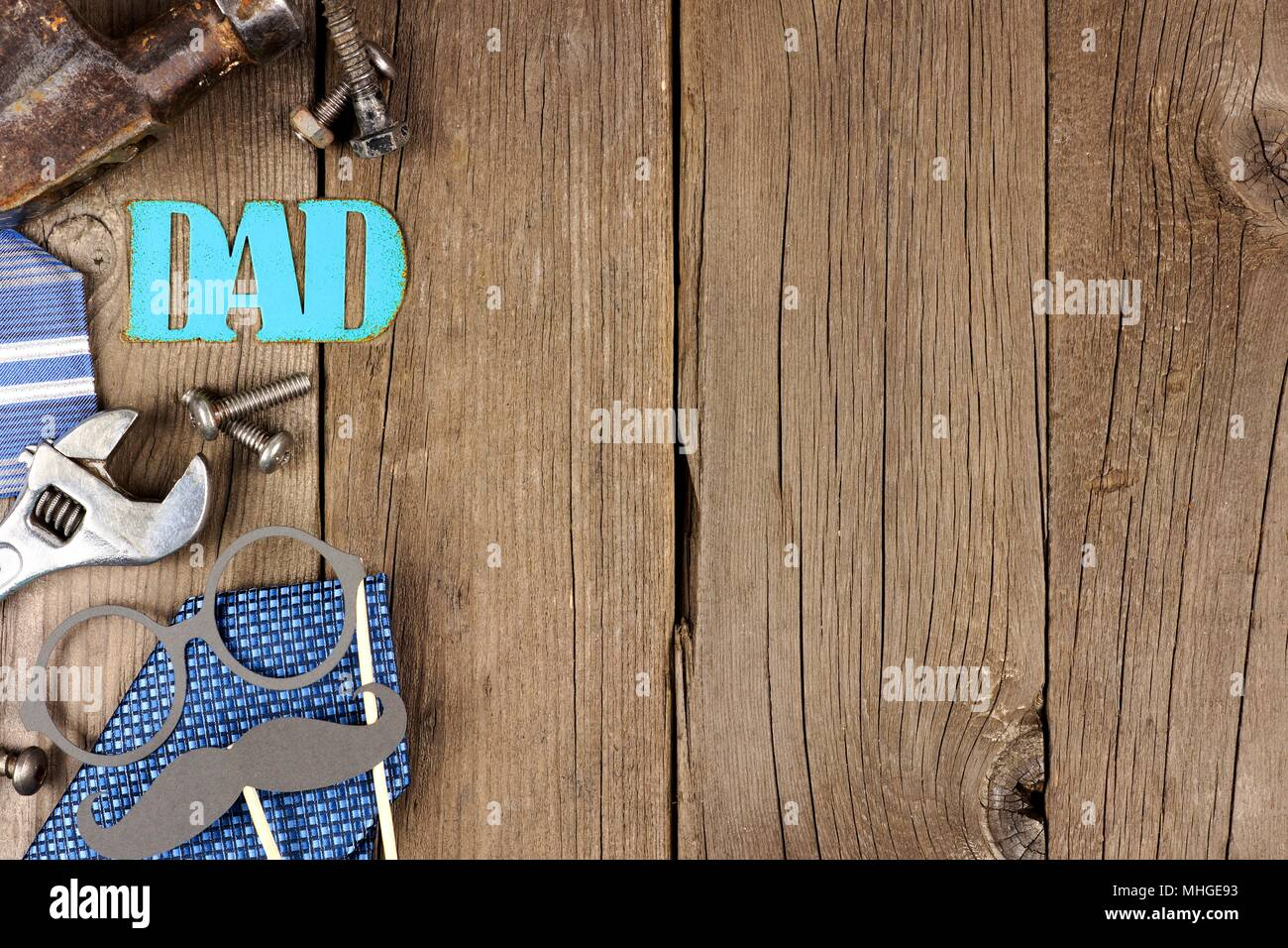 Metallic DAD sign with side border of tools and ties on a wooden background - Stock Image