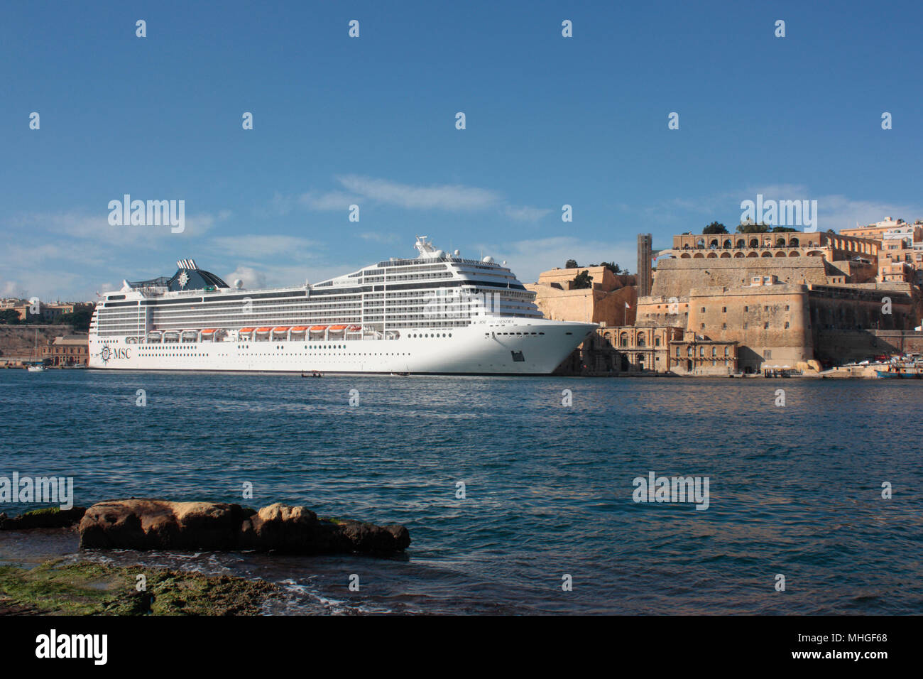 The cruise ship or liner MSC Orchestra in Malta's Grand Harbour next to the Valletta fortifications. Travel and tourism in the Mediterranean Sea. - Stock Image