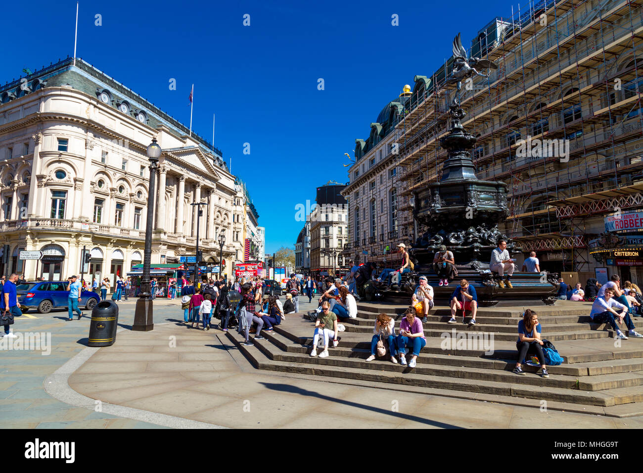 Busy Piccadilly Circus with tourists sitting on the steps of Shaftesbury Memorial Fountain, London, UK - Stock Image