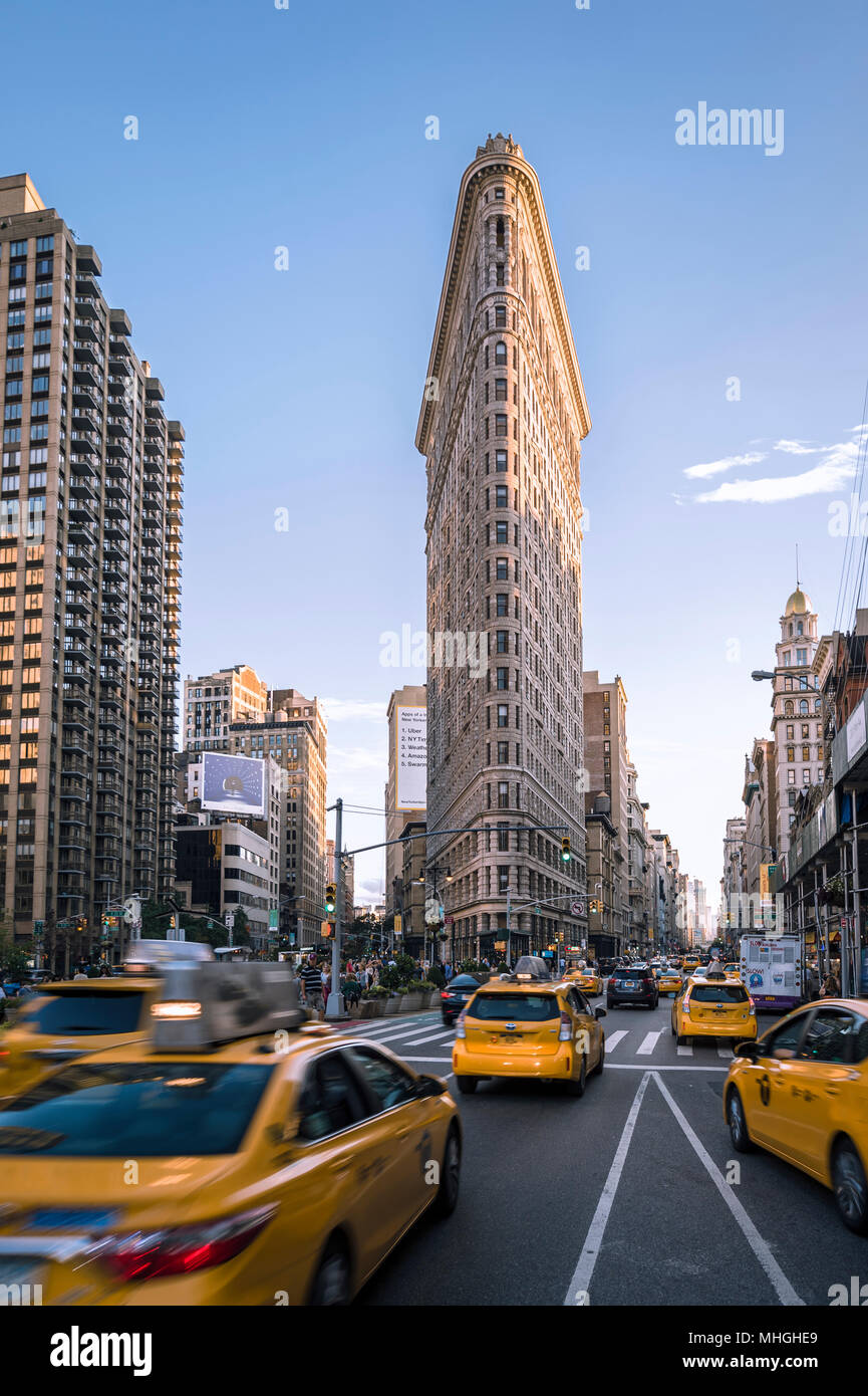 NEW YORK CITY - SEPTEMBER 4, 2016: Yellow taxis pass in front of the Flatiron Building, one of the city's first and most iconic skyscrapers. - Stock Image