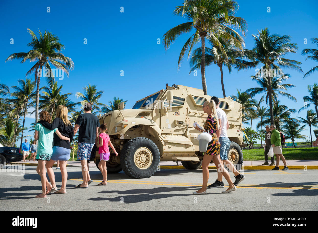 MIAMI - DECEMBER 29, 2017: Tourists pass a large armored military vehicle stationed on Ocean Drive as security is increased for holiday celebrations. - Stock Image