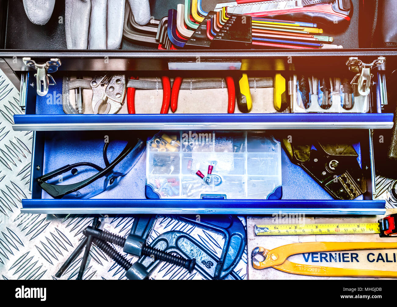 Closeup of tools in box on checkered plate background in workshop. Service tools set. Home building and electrical tools. Plumber hand tools. Technici - Stock Image