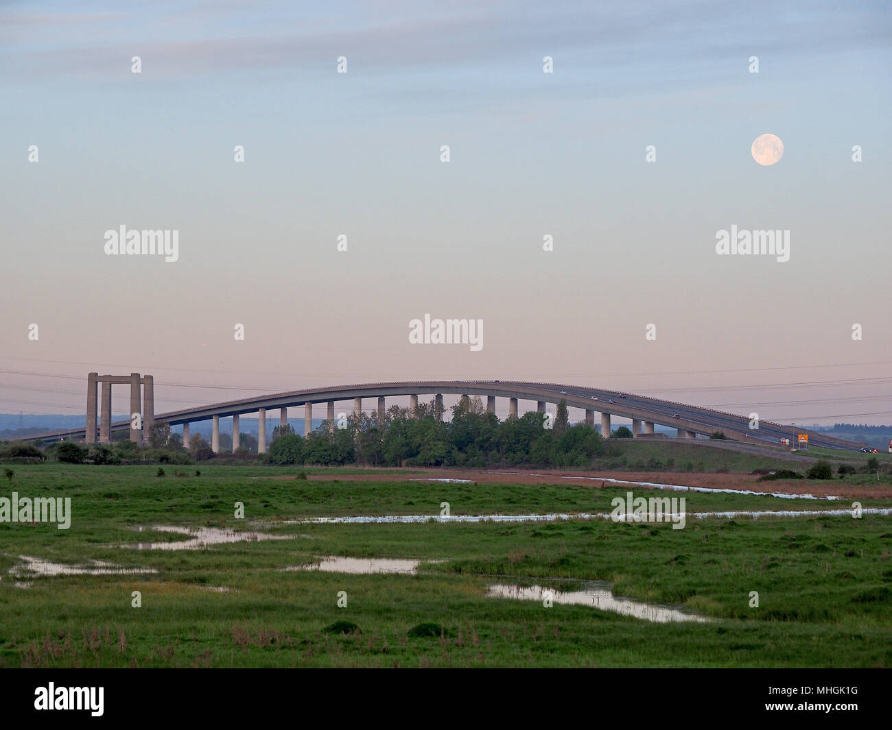 Isle of Sheppey, Kent, UK. 1st May, 2018. UK Weather: the full moon sets over the Isle of Sheppey crossing at sunrise as commuters head to work. Credit: James Bell/Alamy Live News Stock Photo