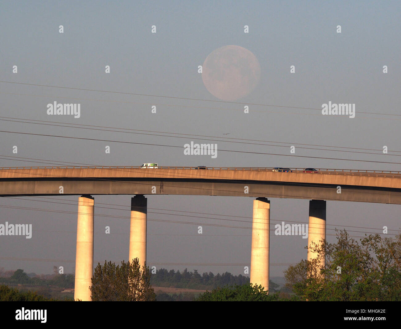 Isle of Sheppey, Kent, UK. 1st May, 2018. UK Weather: the full moon sets over the Sheppey Crossing as the sun rises and commuters head to work.  Credit: James Bell/Alamy Live News Stock Photo