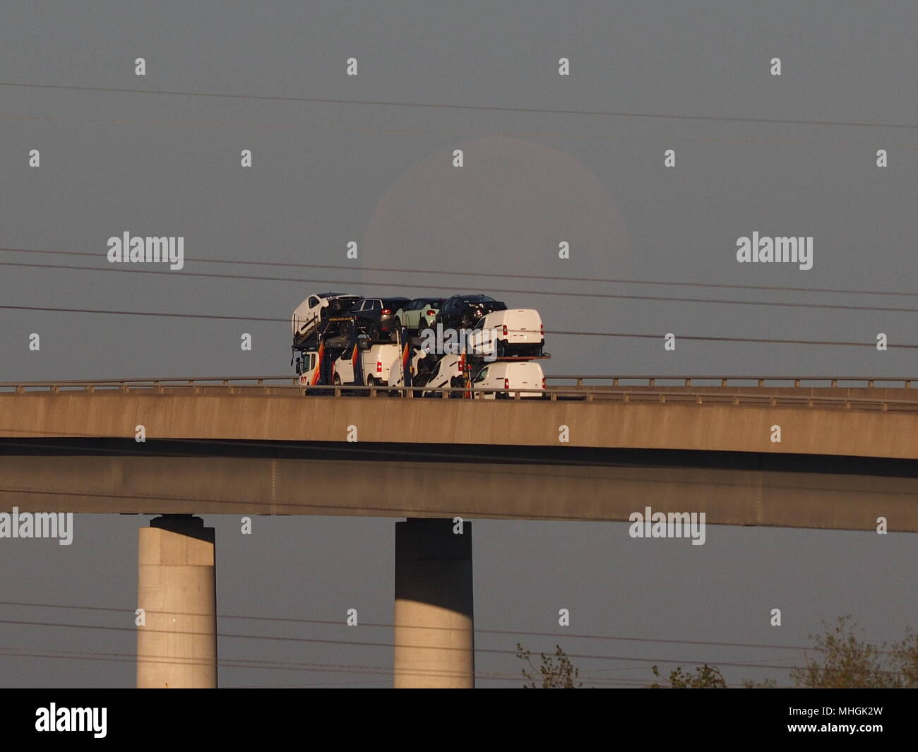 Isle of Sheppey, Kent, UK. 1st May, 2018. UK Weather: a ghostly full moon sets behind a car transporter on the Sheppey Crossing as the sun rises this morning.  Credit: James Bell/Alamy Live News Stock Photo