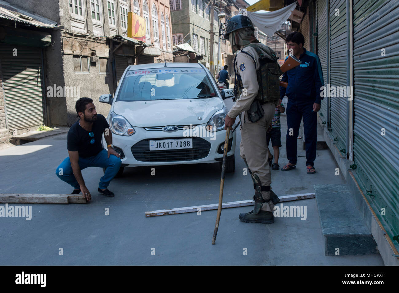 Indian para military troopers stop a vehicle as a  Kashmiri Muslim man tries to remove the wooden logs spread by Indian troops during restrictions in Downtown area of Srinagar city, summer capital of Jammu and Kashmir. Indian authorities on Tuesday imposed restrictions in many parts of Srinagar city  to prevent  clashes and protests in the valley following a protest call by JRL (Joint Resistance Leadership) against killing of a student Shahid Ashraf Dar and two local rebels Sameer Ahmad and Aqib Wani by Indian armed forces and injuring more than 50 innocent unarmed people by using bullets and  - Stock Image