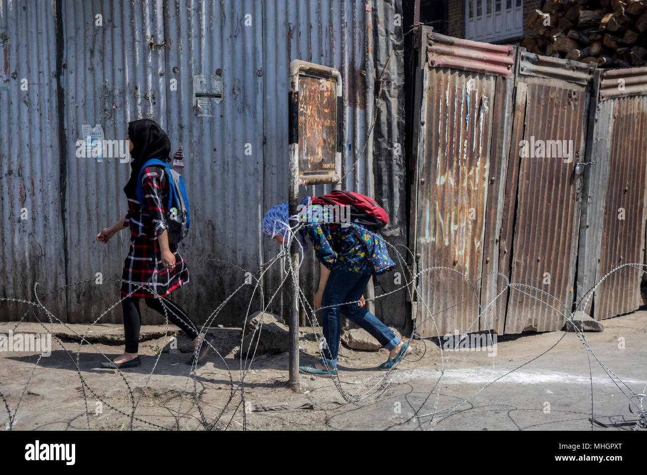 Kashmiri Muslim young girls cross a barbed wire barricade laid by Indian armed forces during restrictions in Downtown area of Srinagar city, summer capital of Jammu and Kashmir. Indian authorities on Tuesday imposed restrictions in many parts of Srinagar city  to prevent  clashes and protests in the valley following a protest call by the JRL (Joint Resistance Leadership) against killing of a student Shahid Ashraf Dar and two local rebels Sameer Ahmad and Aqib Wani by Indian armed forces and injuring more than 50 innocent unarmed people by using bullets and pellets and unleashing a reign of ter - Stock Image