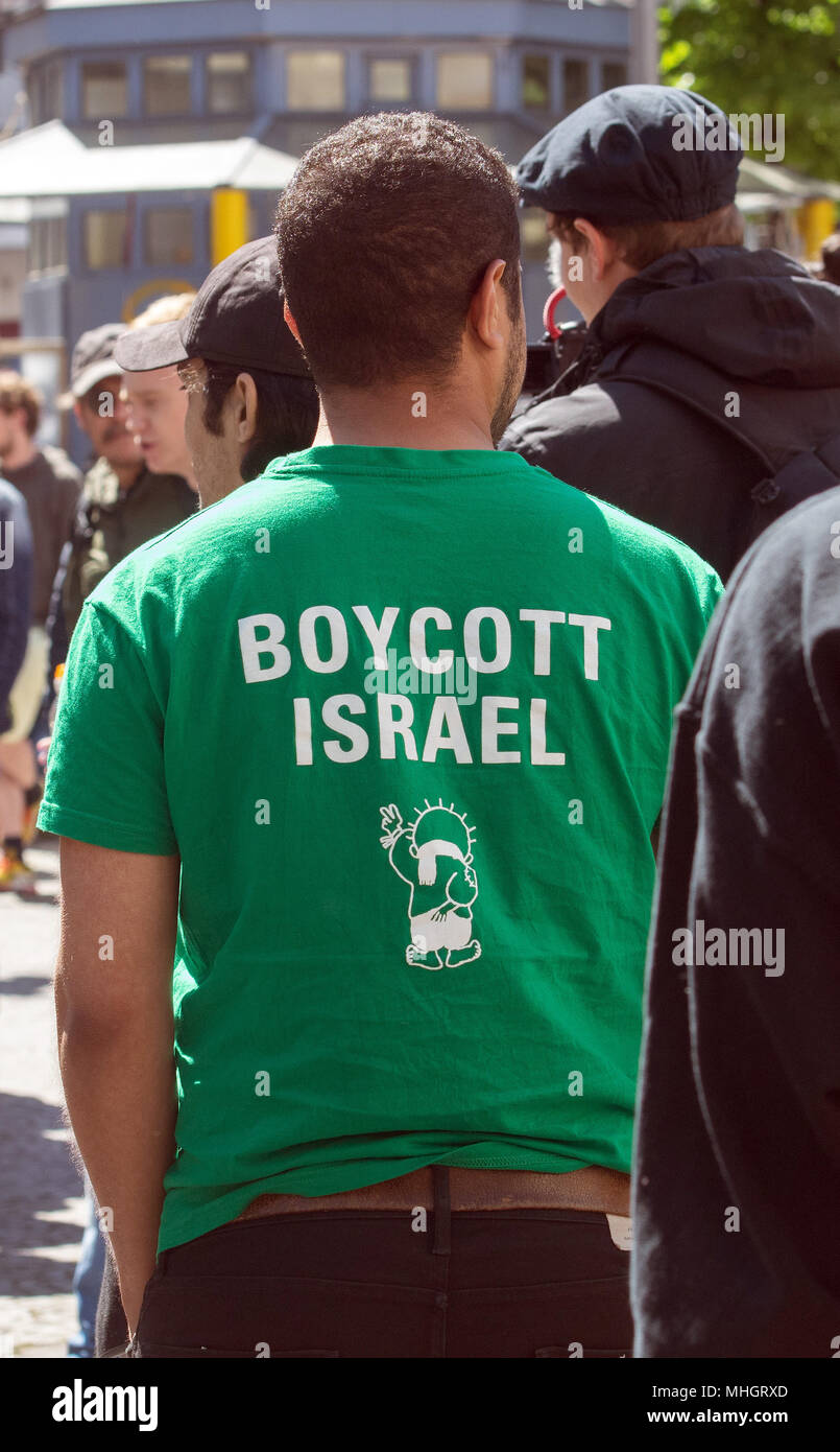 01 May 2018, Germany, Berlin: A protestor wearing a t-shirt reading 'Boycott Israel' at the Karl-Marx-Platz in the district of Neukoelln. According to police reports, more than 100 people with a leftist radical and pro-Palestine background gathered for the demonstration called for by group 'Jugendwiderstand'. Photo: Paul Zinken/dpa - Stock Image