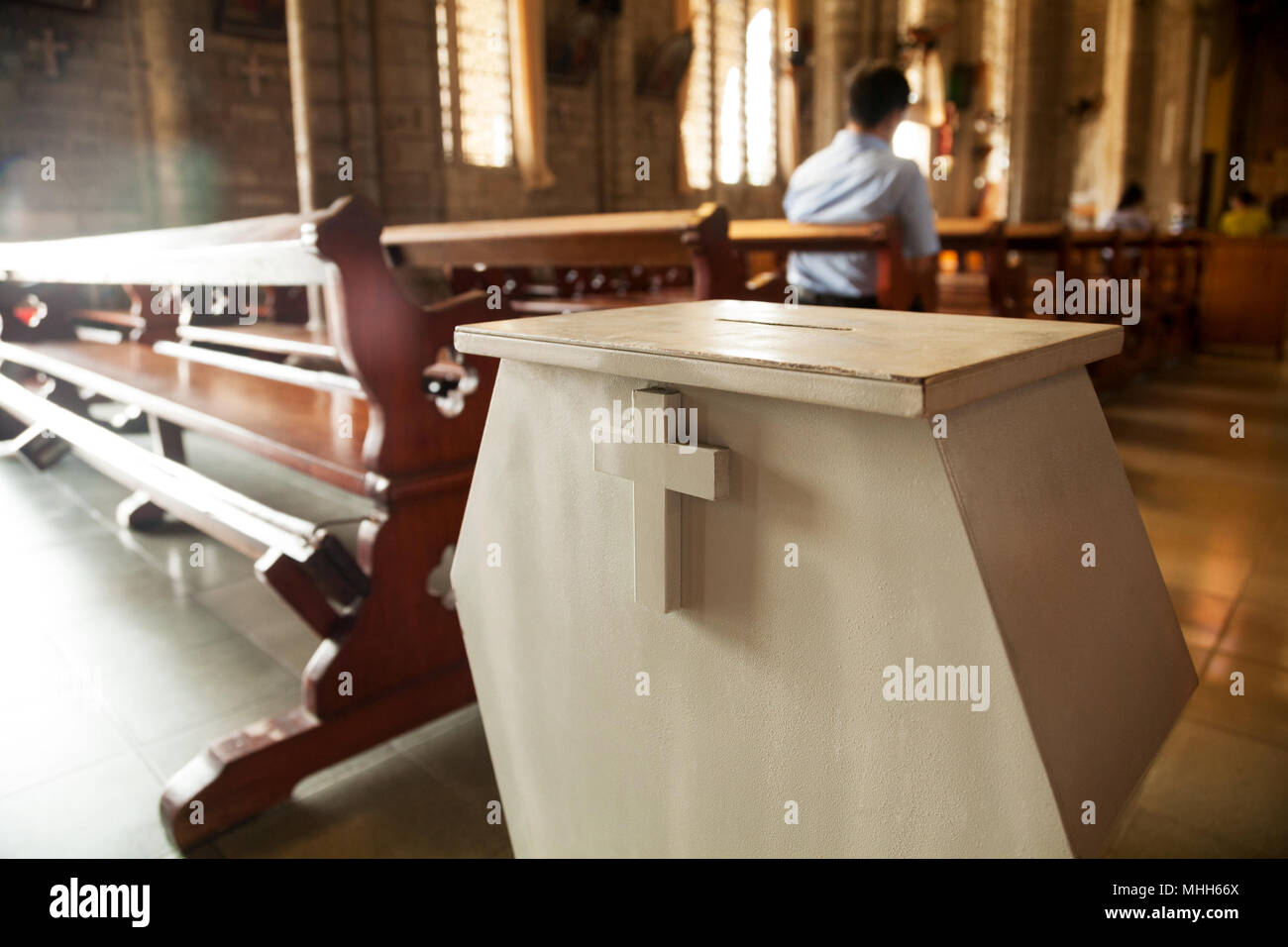 White donation box with a cross on it at a Christian church.  Collection box for generous offertory standing among pews at a Catholic temple - Stock Image
