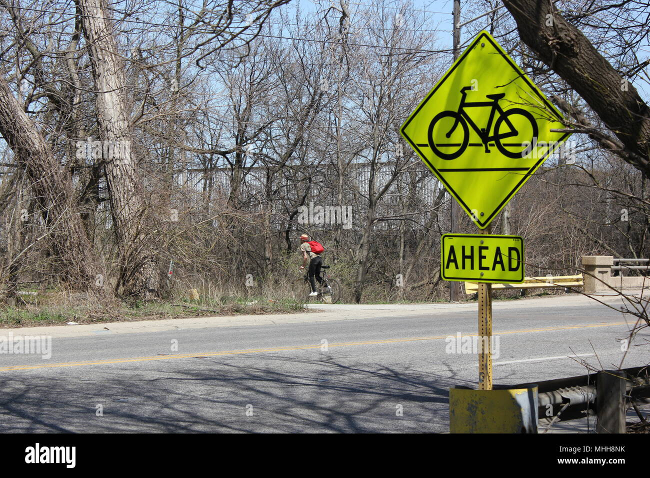 Bicyclist riding thru the cook county forest preserve with a roadway bicycle sign. - Stock Image