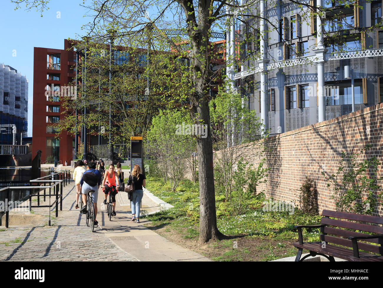 Cycling along the towpath past Gasholder Park, on Regents Canal at Kings Cross, London, UK - Stock Image