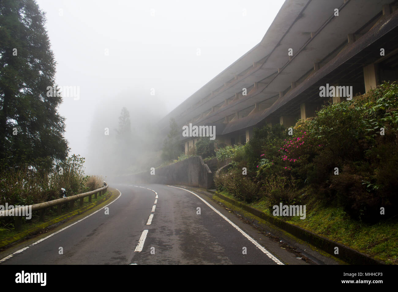 Abandoned hotel on mysterious road with fog - Stock Image