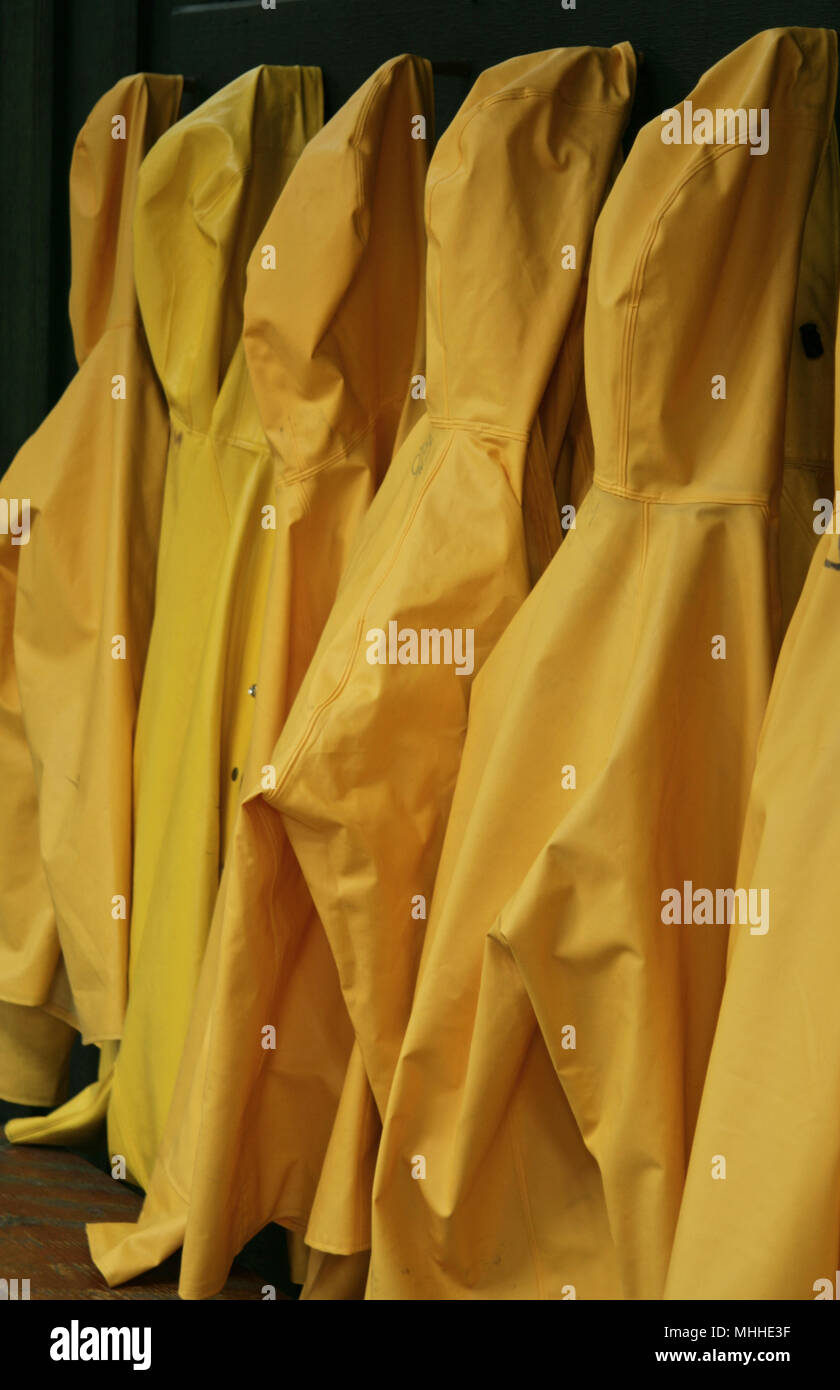 Yellow waterproof jackets hanging up - Stock Image