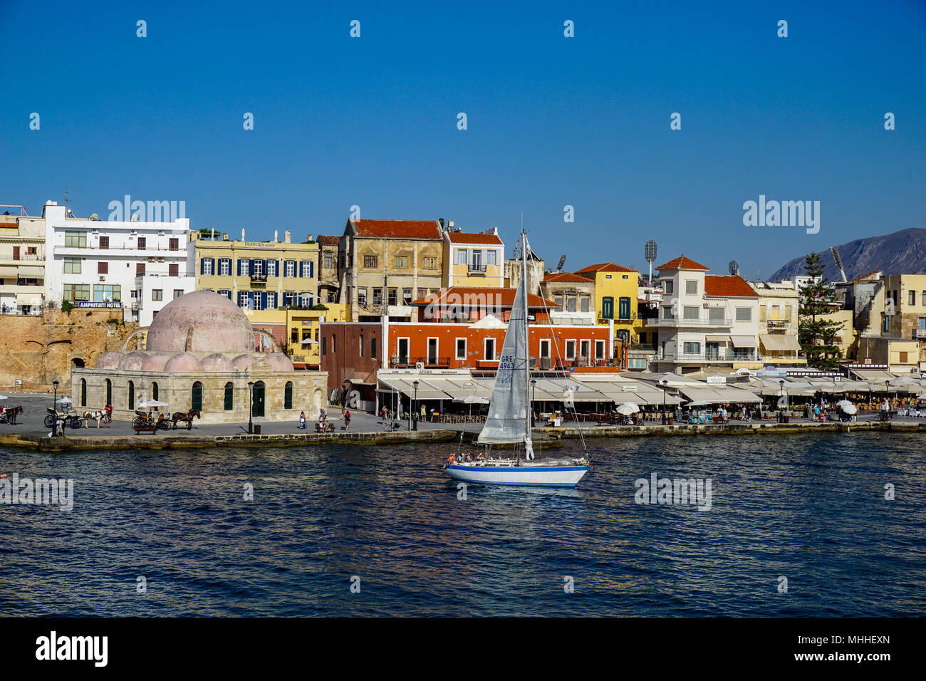Sailboat in harbor in Chania, Crete with Mosque of Janissaries in background Stock Photo