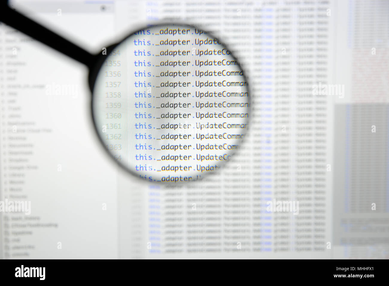Real c# code developing screen. Programing workflow abstract algorithm concept. Lines of c# code visible under magnifying lens. Stock Photo