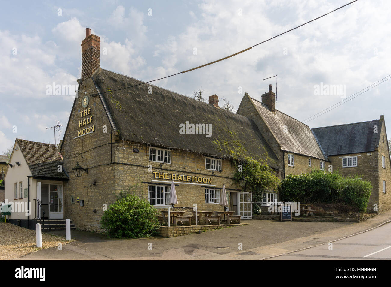 The Half Moon, a traditional thatched pub, in the Northamptonshire village of Grendon, UK - Stock Image