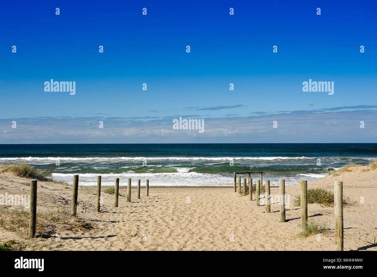 Pathway to the waves, Seven Mile Beach, NSW, Australia. Beautiful seascape, sandy track through the dunes, aquamarine water, white surf, deep blue sky - Stock Image