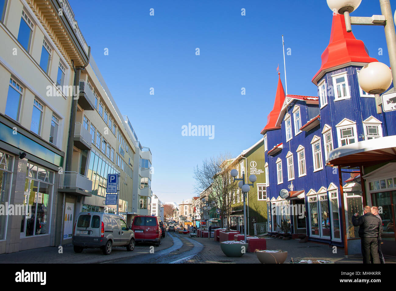 Colourful buildings in the main street, Akureyri city centre, Iceland. People and parked vehicles in Hafnarstraeti pedestrian mall - Stock Image