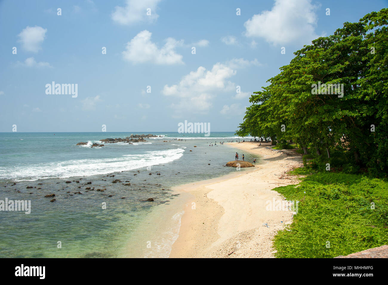 Galle Beach in the old town of Galle. Breathtaking scene, gentle surf breaking over rocks along the reef, blue sky and a green treeline and foreground - Stock Image