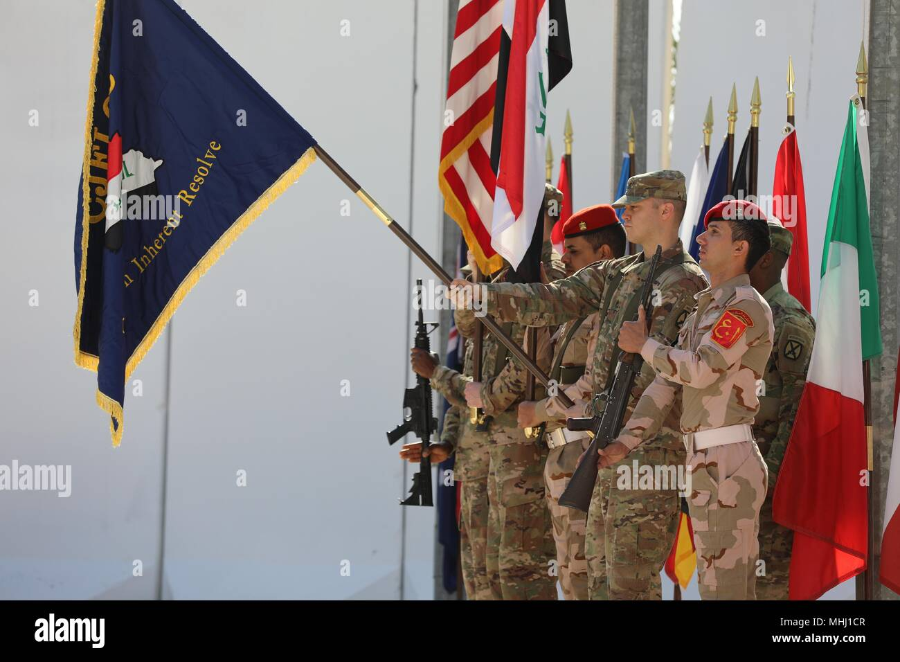 Coalition members with the Combined Joint Forces Land Component Command color guard render a salute during the CJFLCC deactivation ceremony at Baghdad, Iraq, April 30, 2018, April 30, 2018. The deactivation signifies the end of major combat operations against ISIS in Iraq and acknowledges the changing composition and responsibilities of the Coalition. (U.S. Army photo by Sgt. Jonathan Pietrantoni). () - Stock Image