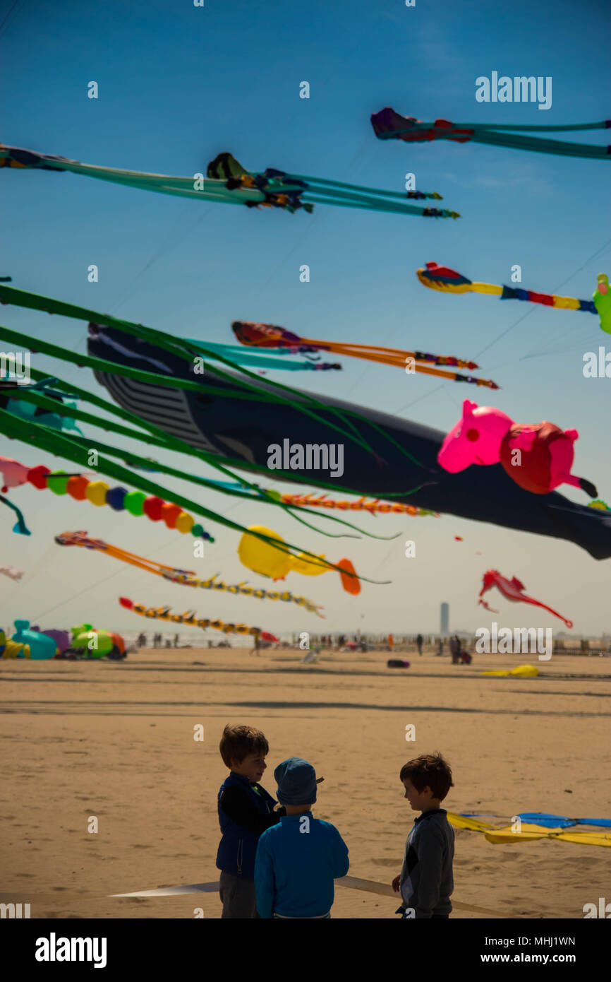 CERVIA, APRIL 2018: children watching colorful kites in different shapes on the beach at Cervia international kite festival 'Artevento' 2018. Vertical - Stock Image