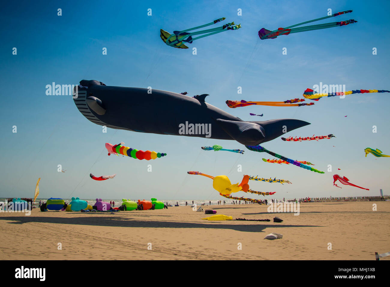 Many colorful kites in different shapes on the beach at Cervia international kite festival 'Artevento' 2018. - Stock Image