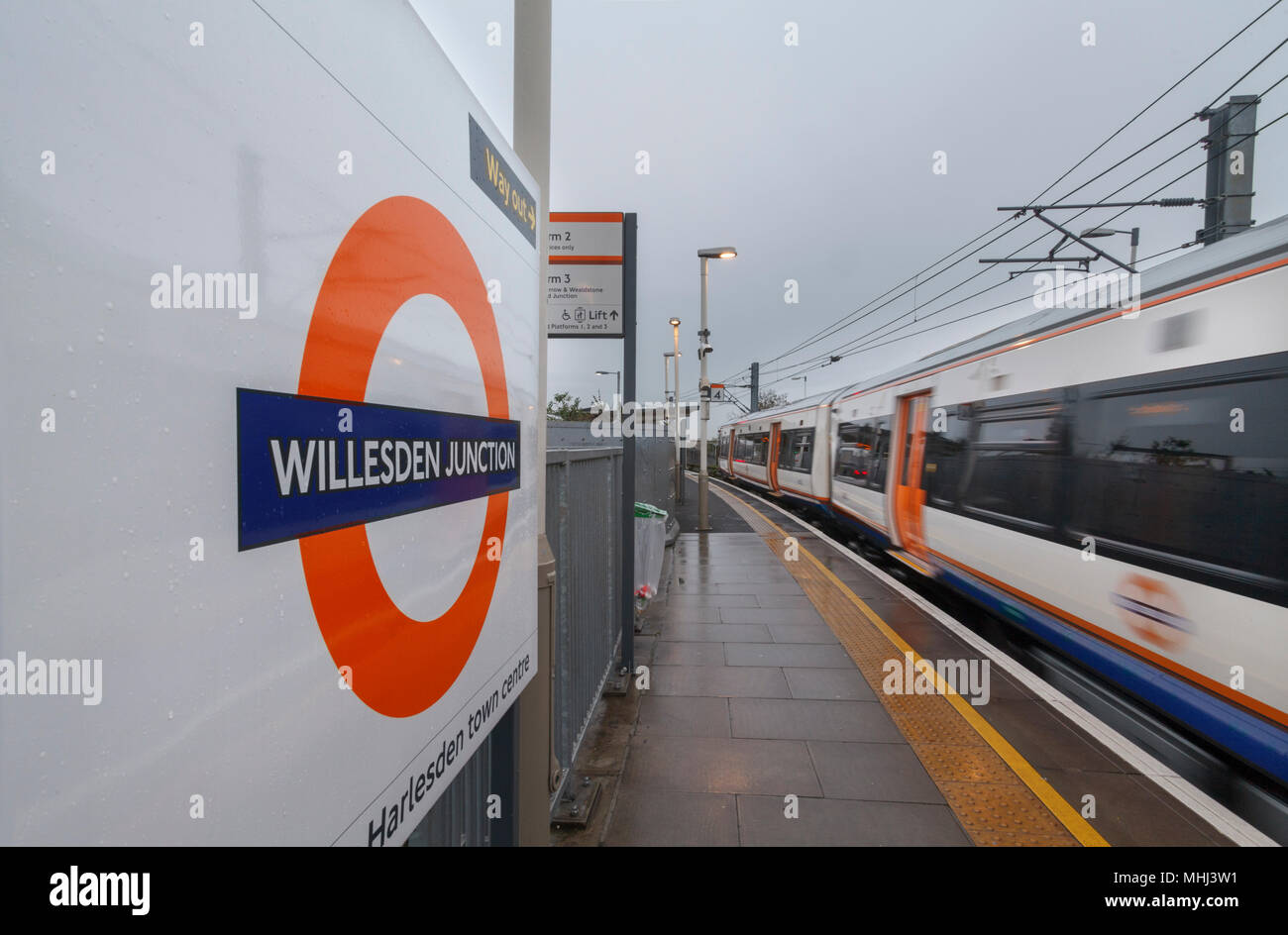 A London Overground class 378 capital star train departing Willesden Junctionn High level with the station sign and overground logo - Stock Image