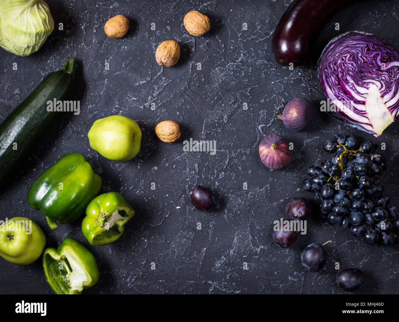 Fresh organic raw green and purple colored vegetables and fruits on ...