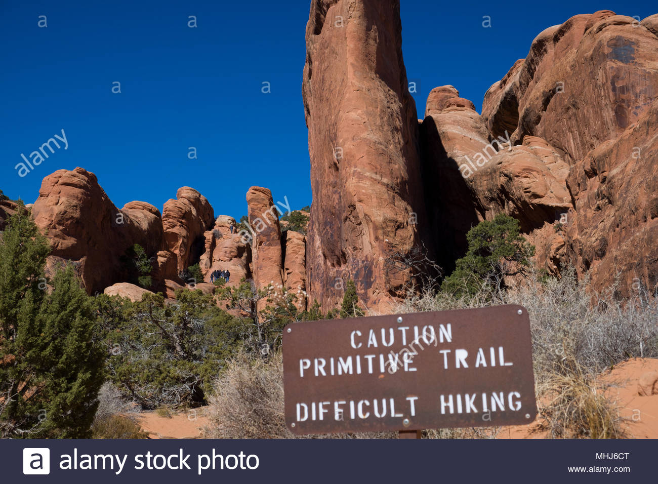 Metal sign cautioning about primitive trail with difficult hiking conditions on the Devils Garden Trail in Arches National Park, Grand County, Utah, U - Stock Image