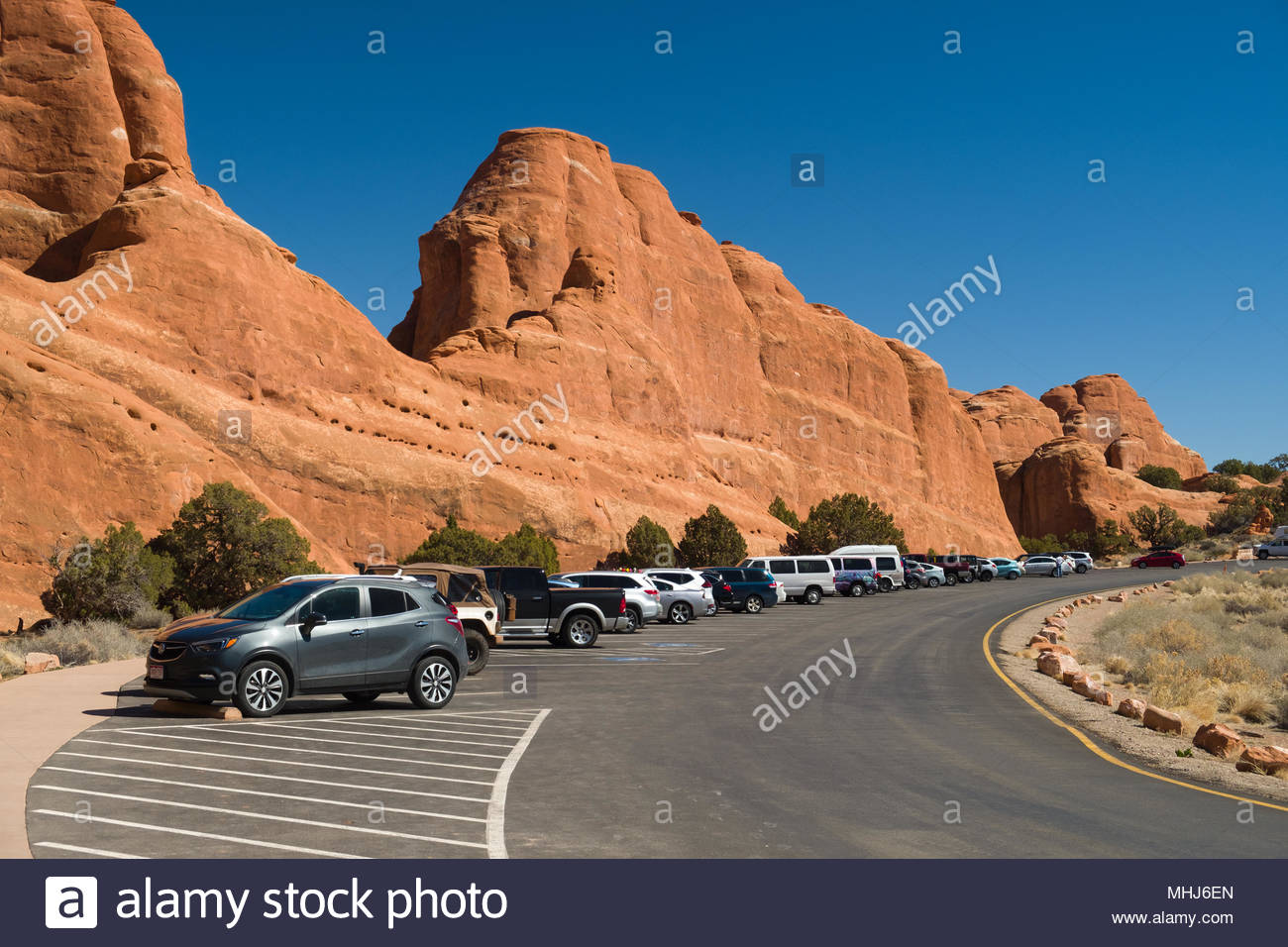 Cars, vans and SUV automobiles parked at the Devils Garden trailhead in Arches National Park, Grand County, Utah, USA - Stock Image
