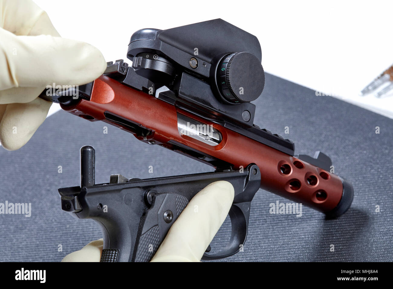 Gloved hands taking apart a 22 pistol in preparation to cleaning it - Stock Image