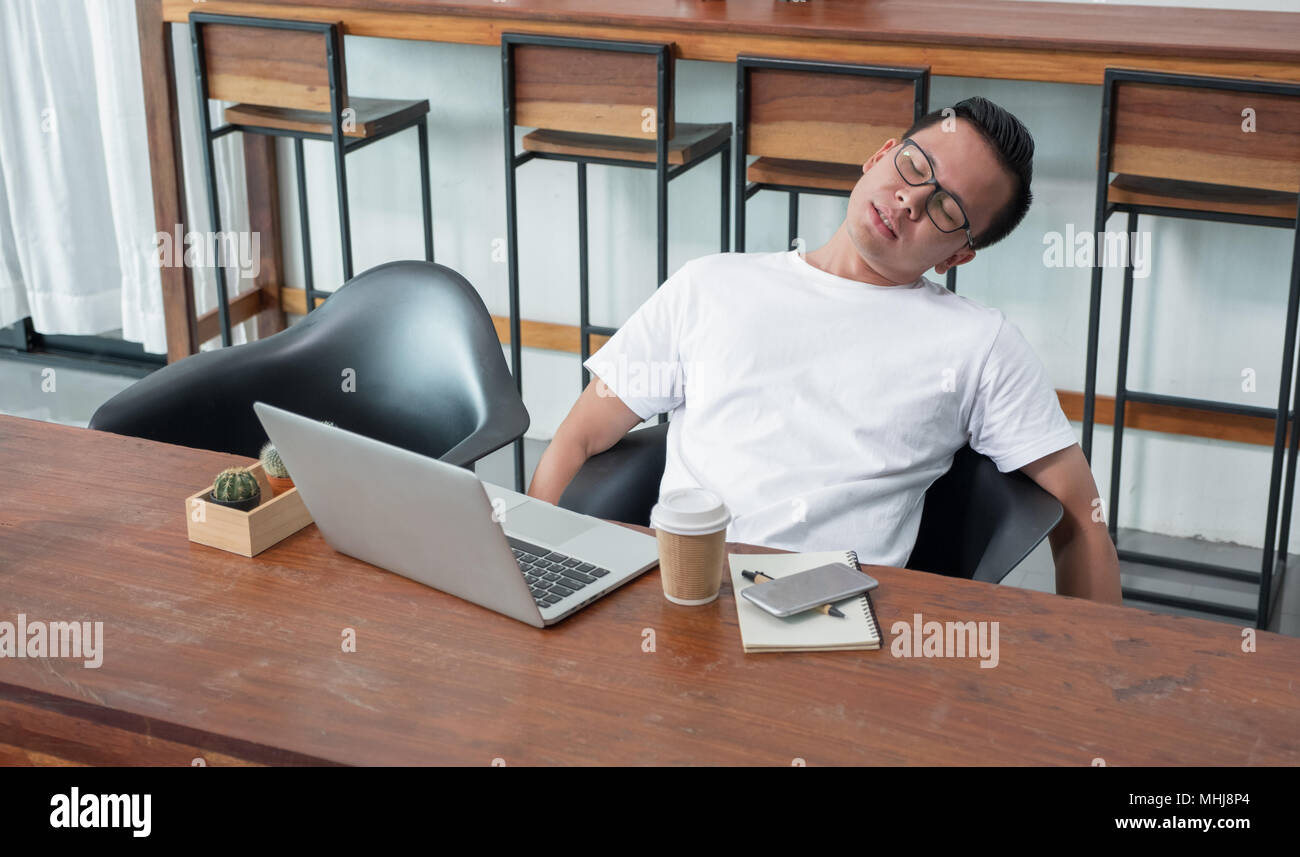 asia casual man sit back feel tired from work at laptop in coffee shop,stress business concept,work outside office,work at home - Stock Image