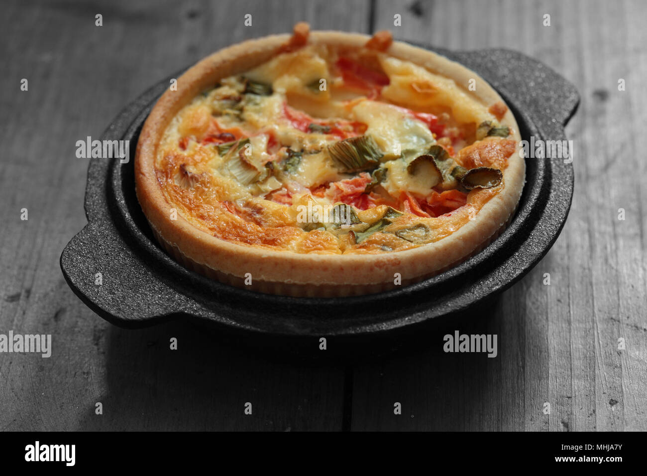 Tomato and spring onion quiche in a cast iron pot dish on a wood background with selective color - Stock Image