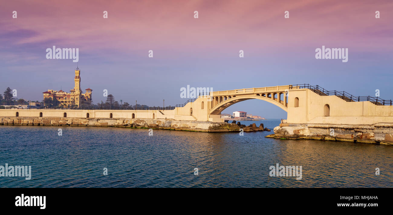 Panoramic view of bridge in the sea at Montazah park with the Royal palace in the far distance with calm sea at sunrise time, Alexandria, Egypt - Stock Image