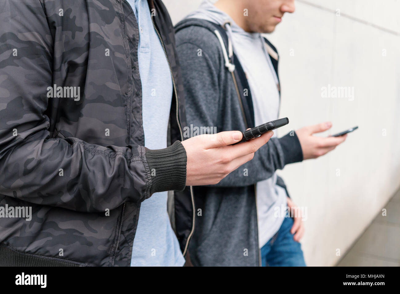 two antisocial mobile phone addicted male teenagers using smartphone, technology concept, leaning against wall with copy space - Stock Image