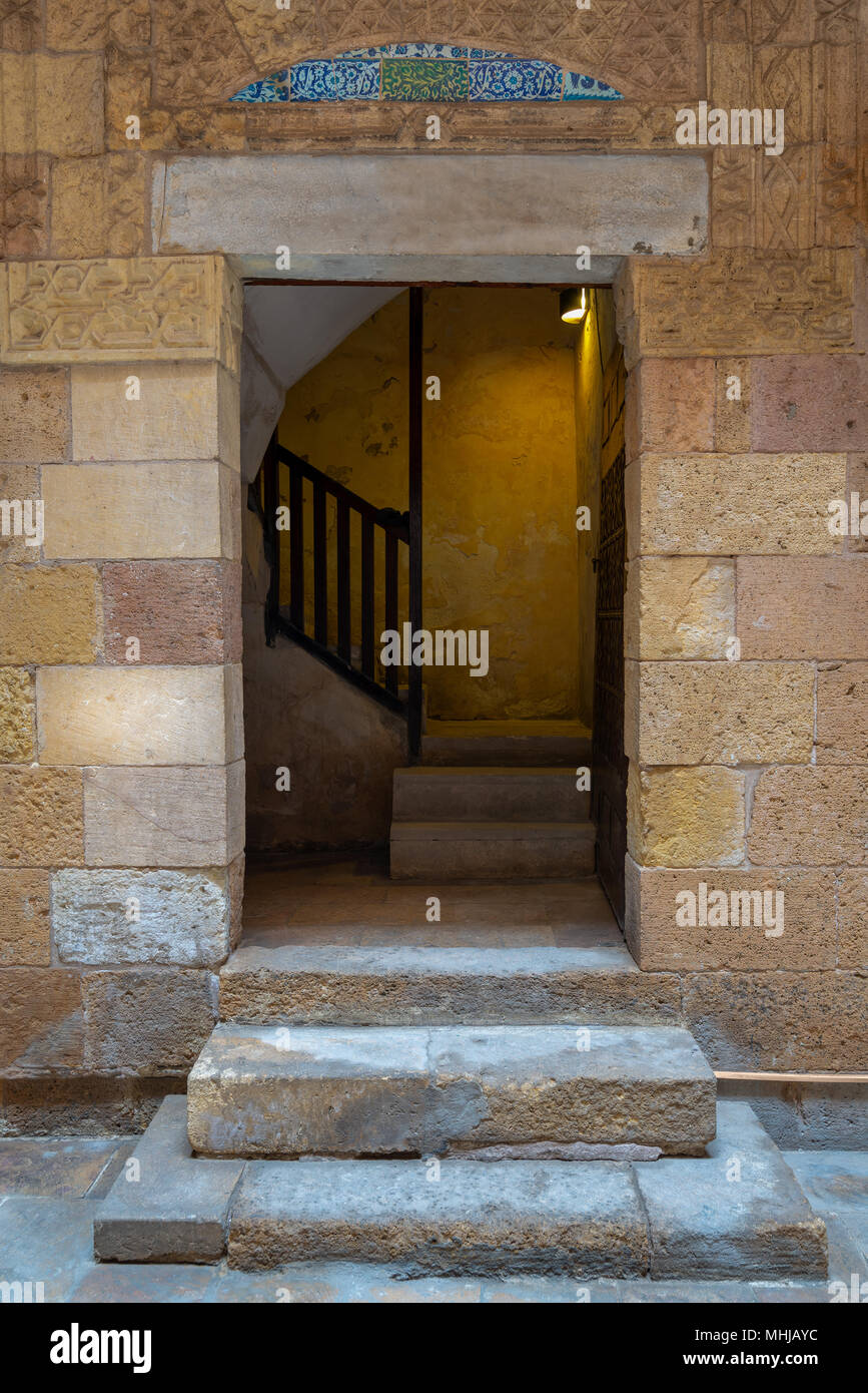 Ancient external old decorated bricks stone wall and doorway leading to the House of Egyptian Architecture historical building, Cairo, Egypt - Stock Image