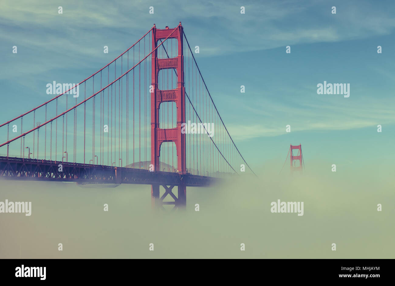 Thick low fog formed under the Golden Gate Bridge in San Francisco, California, United States, on an early spring morning. - Stock Image