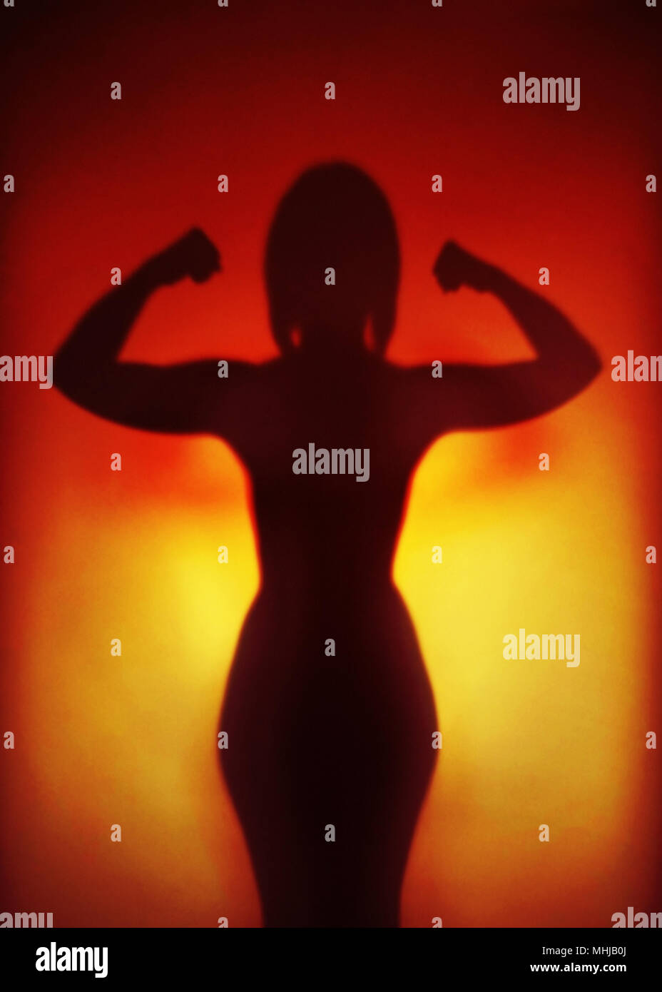 female empowerment or feminism or emancipation concept, silhouette of an anonymous strong woman flexing muscles - Stock Image