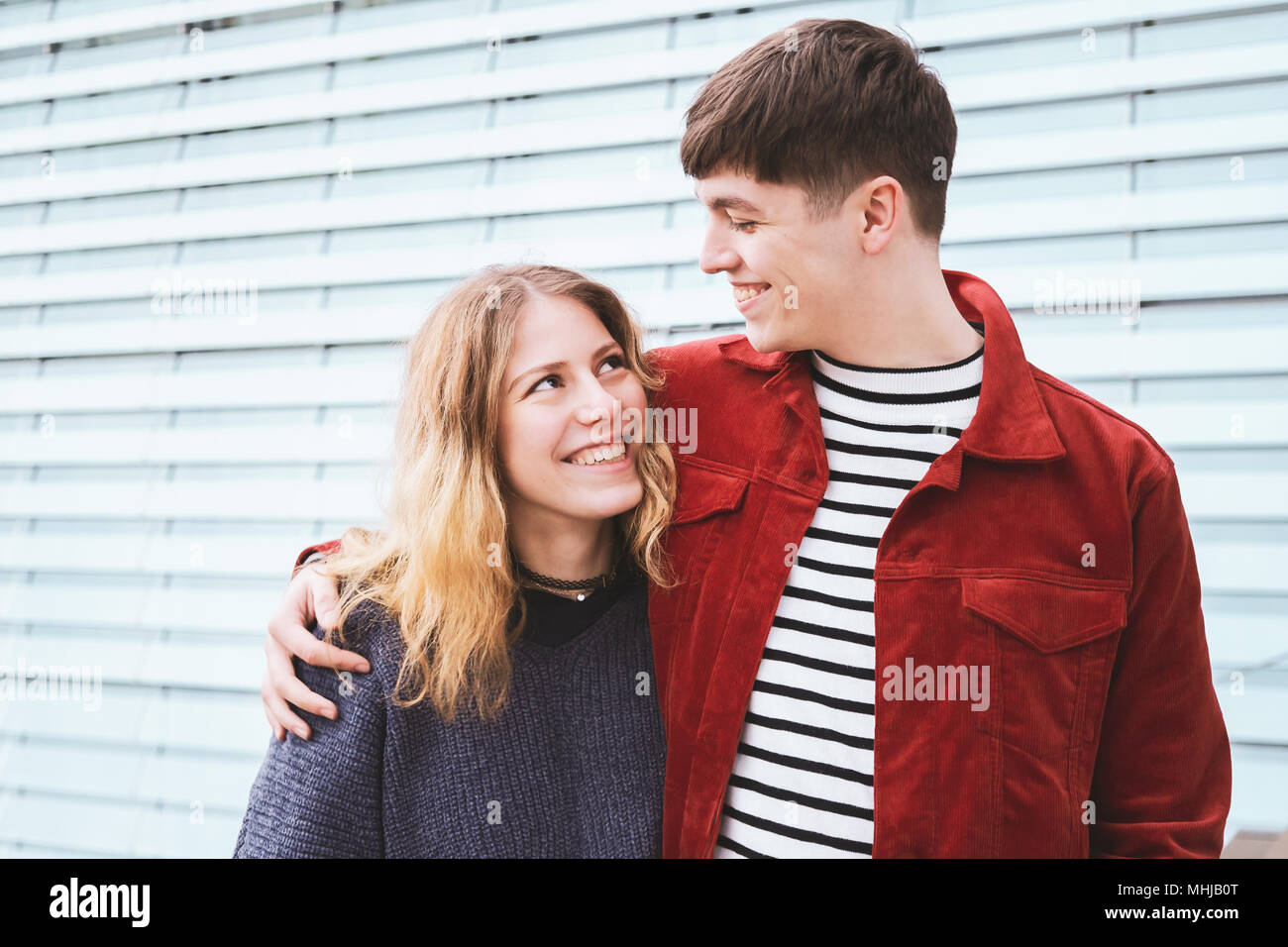 teenage couple in love looking into each others eyes, urban setting with copy space - Stock Image