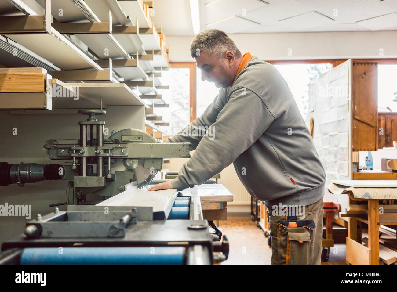 Tinner working on metal sheets in his workshop - Stock Image